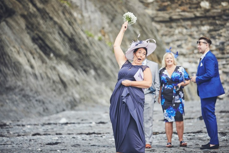 documentary wedding photography of guest laughing at Tunnels Beaches in devon