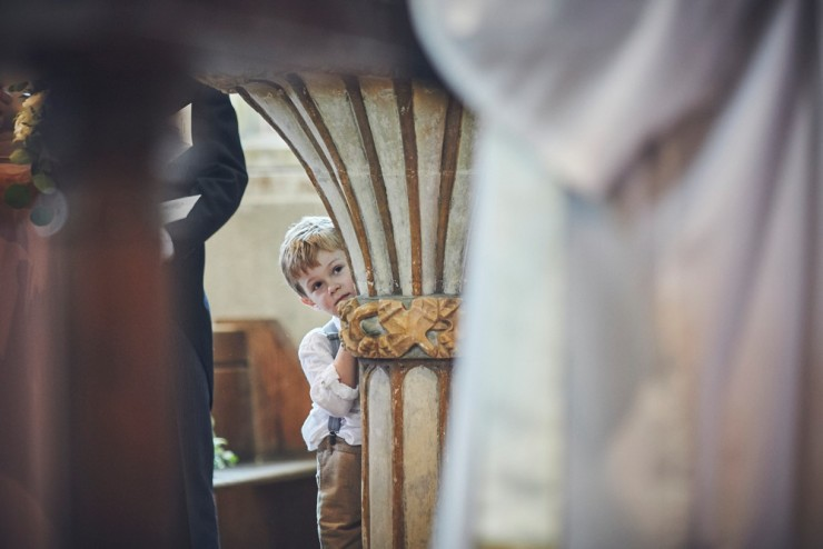 documentary wedding photography of little boy peeping at bride and groom south hams wedding in devon