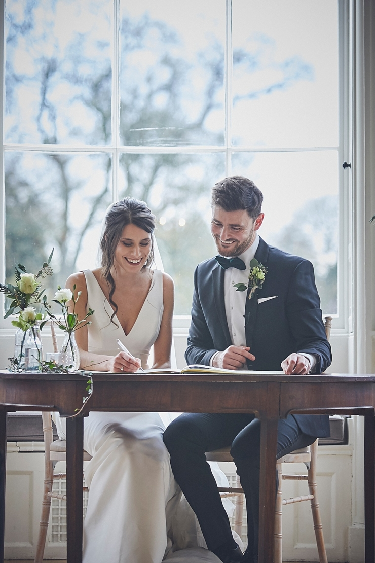 bride and groom happy signing register at wedding ceremony at small devon wedding