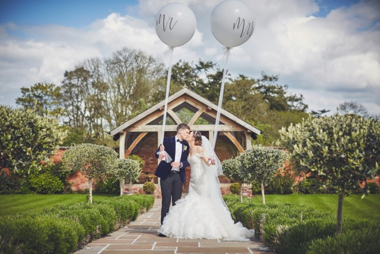 relaxed wedding photography of bride and groom with balloons at upton barn and walled garden devon