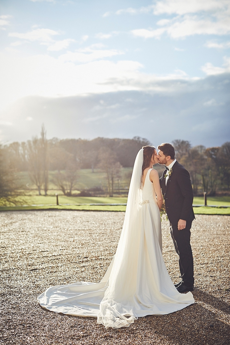 portrait of bride and groom kissing at small winter wedding at Rockbeare manor in Devon