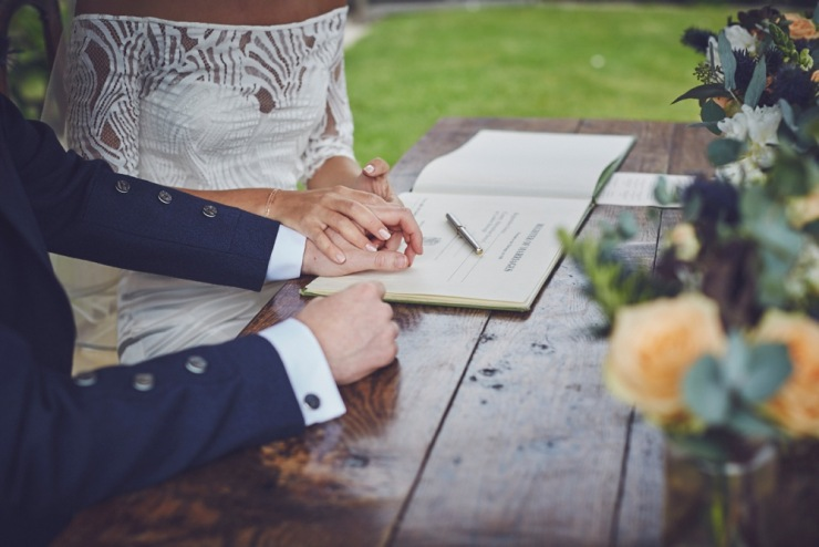 candid wedding photography of signing the register Kingston Estate Devon