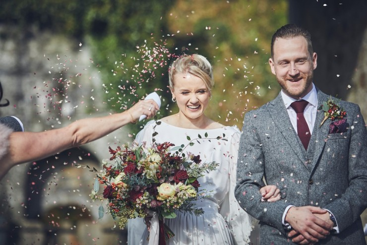 Devon team of two wedding photographers capture confetti throw at an Autumn wedding in the barn at Hotel Endsleigh in Devon
