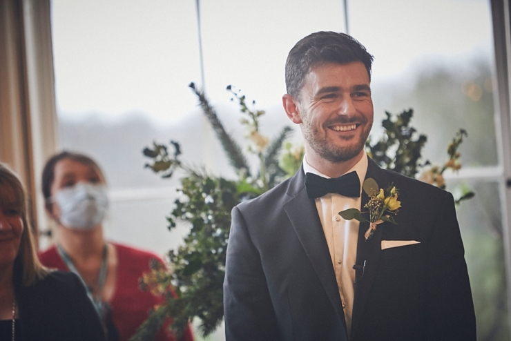 wedding photography of groom smiling at bride to be at small Rockbeare manor devon wedding