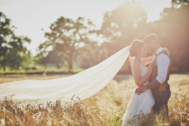 portrait bride and groom in field of corn or wheat at sunset at Upton Barn and Walled Garden in Devon