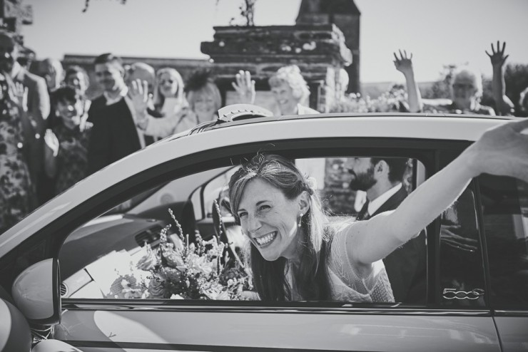 reportage photography bride waving out car window at South Hams wedding