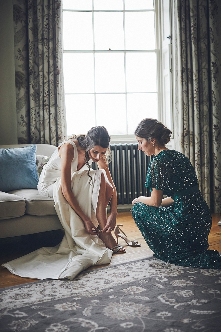 bride putting on her wedding shoes with her bridesmaid at Rockbeare manor in Exeter