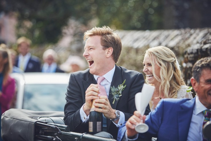 bride and groom laughing as groom pops champagne at a south hams wedding in devon