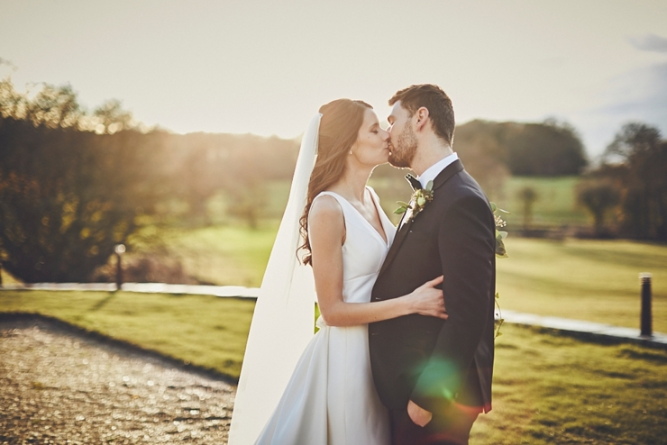 bride and groom kissing in golden hour sunlight at small winter wedding at Rockbeare manor in Devon