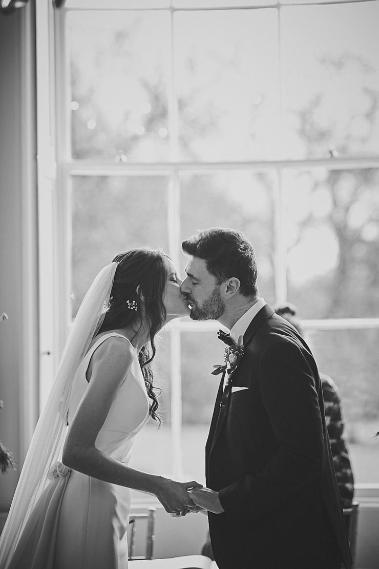 bride and groom first kiss at small wedding at Rockbeare manor in Devon