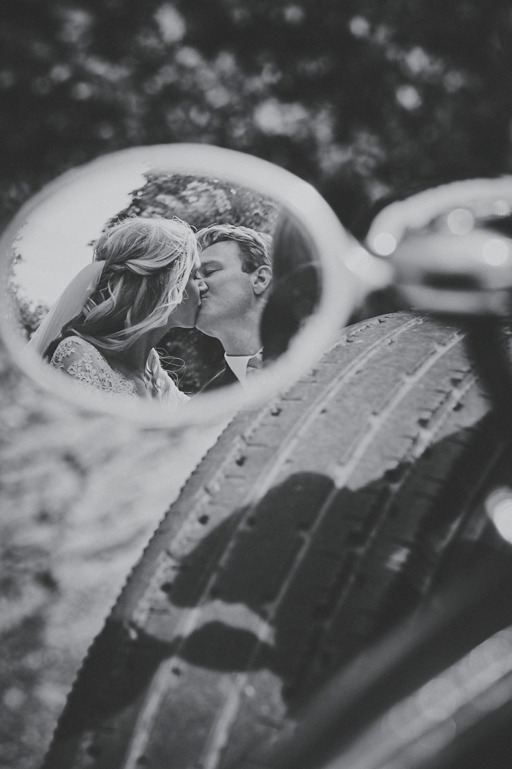 reflection of happy couple kissing in the wing mirror of vintage rolls Royce at a wedding in Devon