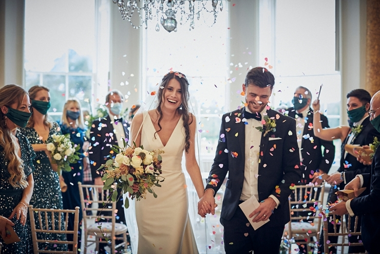 bride and groom walking through indoor confetti shower at small devon wedding at Rockbeare Manor