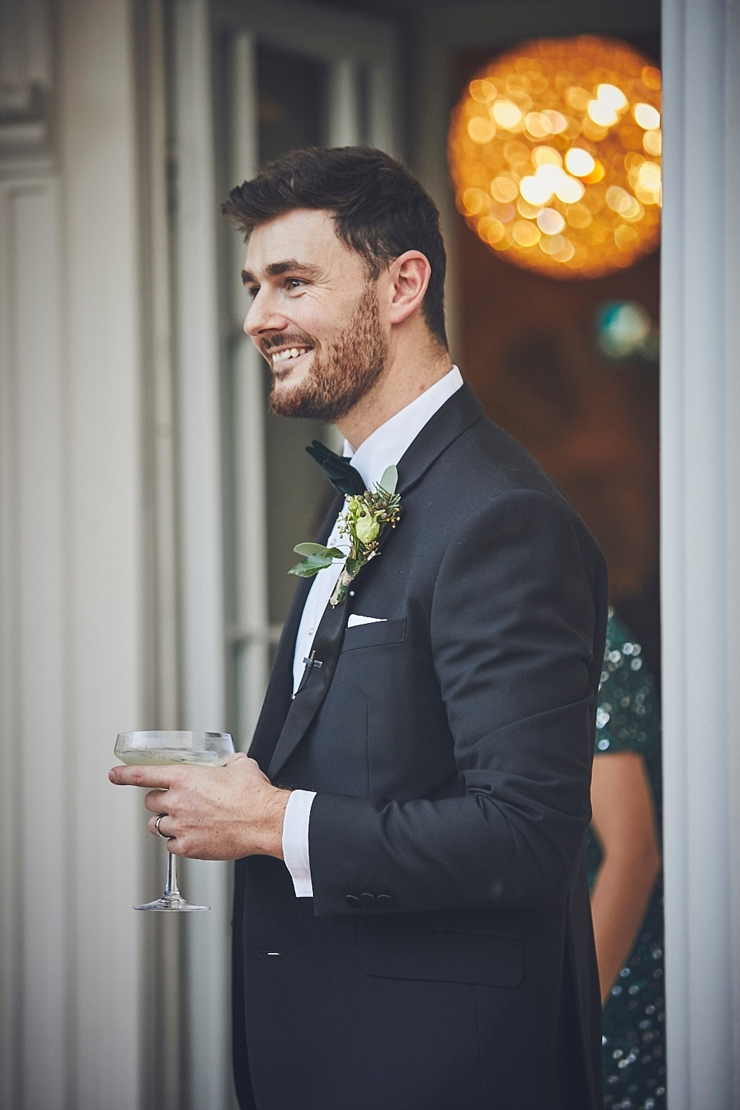 relaxed wedding photography and happy groom wearing black tie at mini wedding in Devon