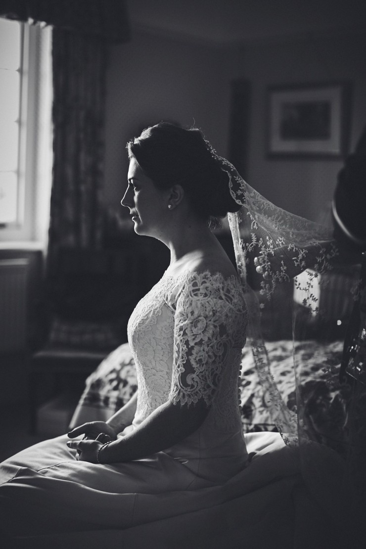 black and white wedding photography of Devon bride seated with veil