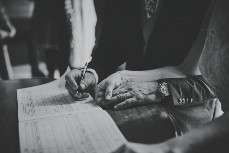 documentary photography of a hand holding signing register at a wedding at Rockbeare Manor near Exeter in Devon