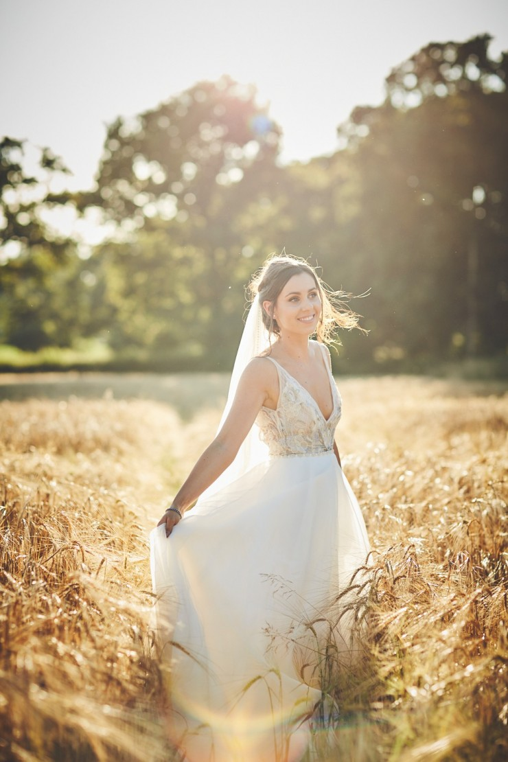 portrait of bride holding her wedding dress in field of corn or wheat at sunset at Upton Barn and Walled Garden in Devon