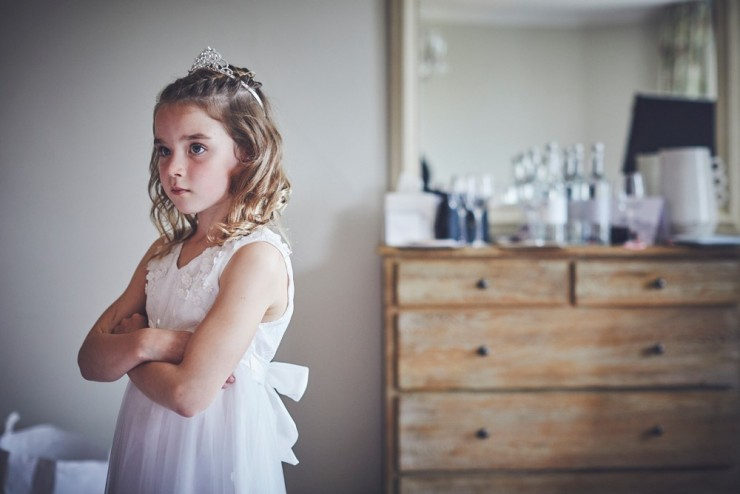 documentary photography of flower girl looking stern at a wedding at Rockbeare Manor near Exeter in Devon