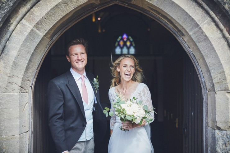 bride and groom laughing as they come out of the church at a south hams wedding in devon