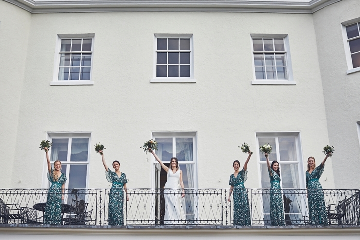 bridal party waving from balcony at a mini wedding at Rockbeare Manor in Devon