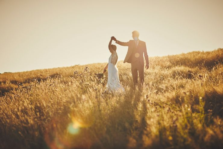 wedding photography of a bride and groom dancing in a corn filed at sunset