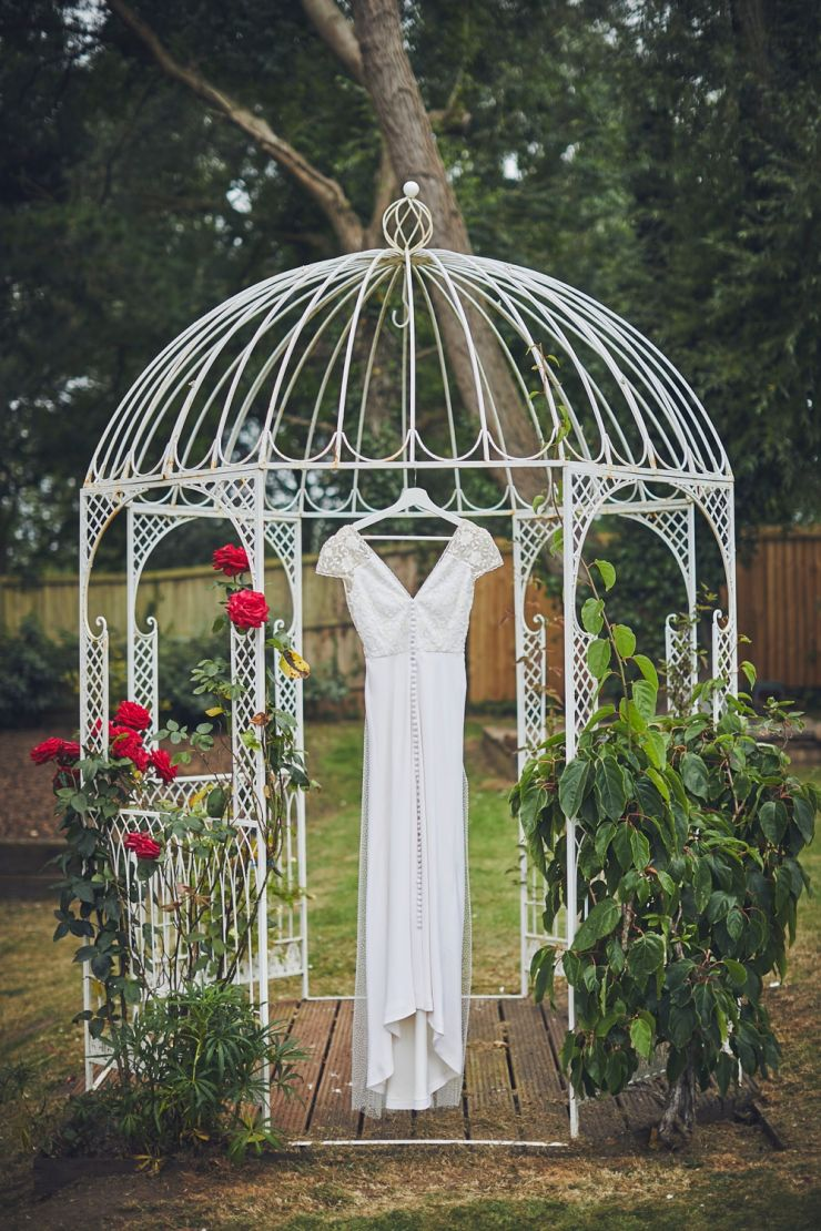 wedding gown hanging from rose covered pergola