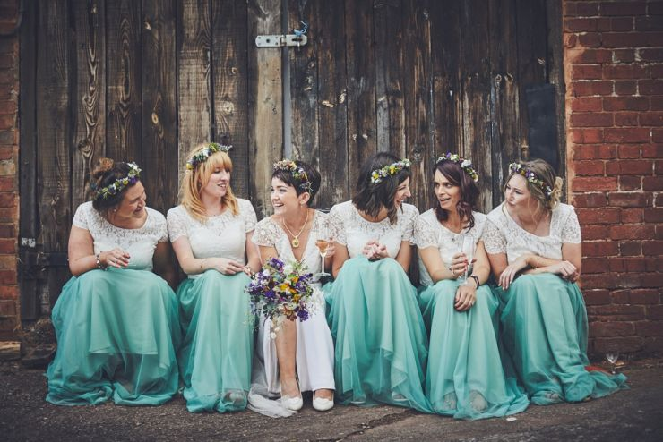 bridesmaids and bride sat together laughing at a Devon wedding at West Town farm