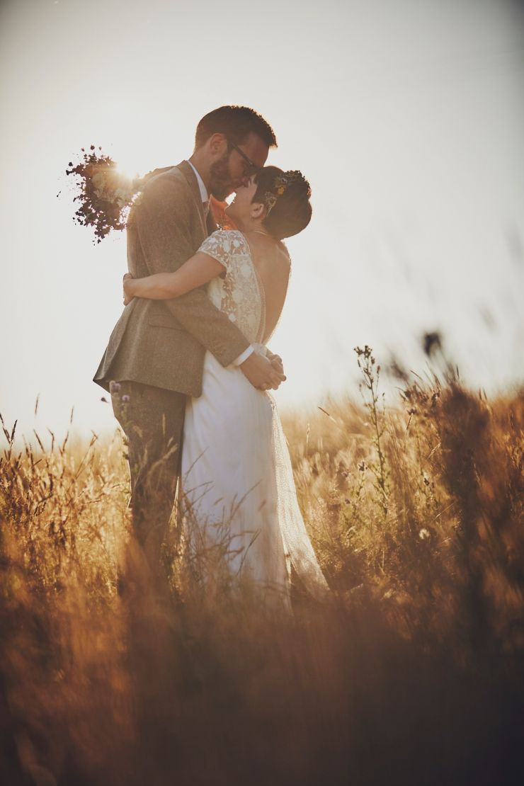bride and groom kissing in Devon field at golden hour