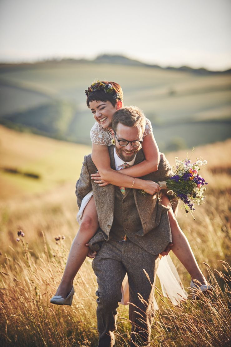 bride having a piggy back and laughing at Devon wedding at sunset