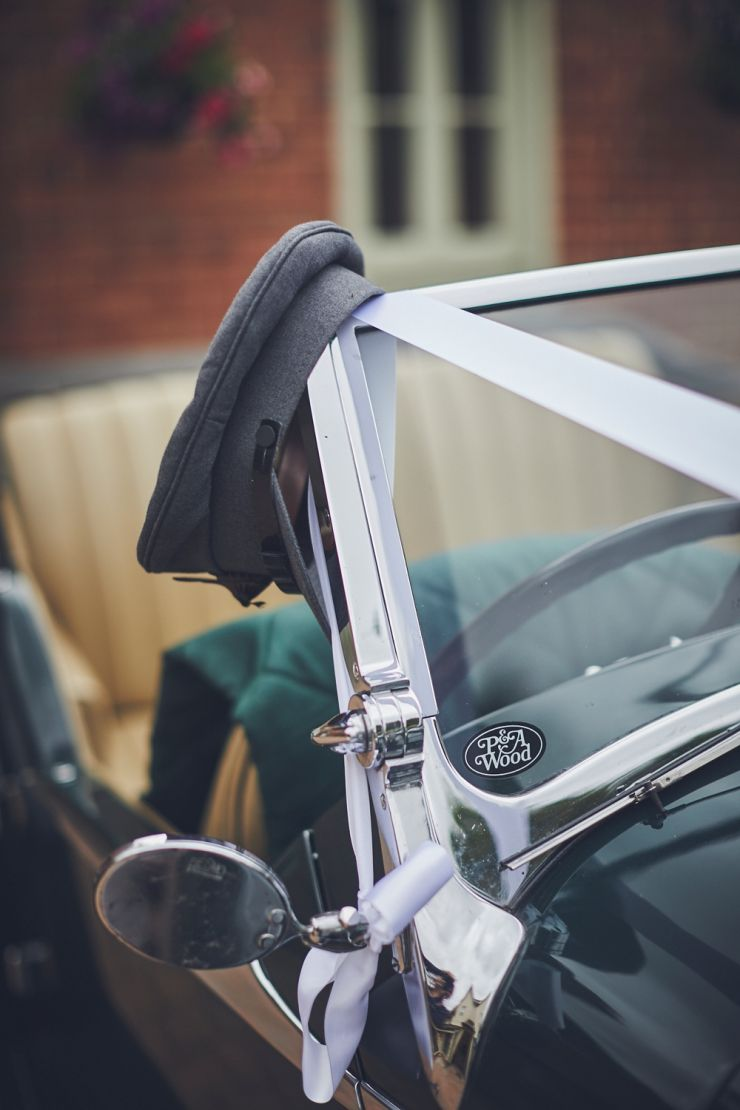 chauffeur's hat hanging on vintage wedding car window in Exeter