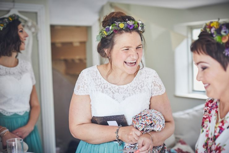 bridesmaid laughing wearing white lace top and green skirt and bright flower crown
