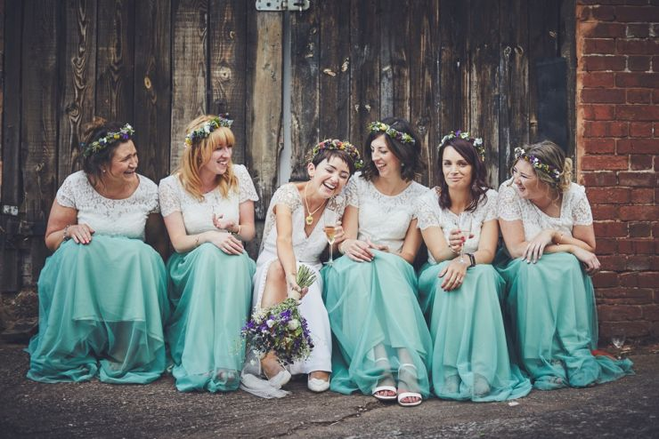 fun wedding photography of bridesmaids and bride sat together laughing at a Devon wedding at West Town farm