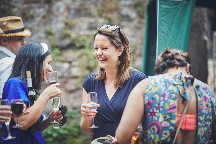 relaxed wedding photography of guests laughing at a wedding at a West Town Farm devon