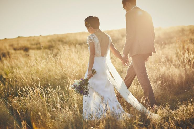 documentary wedding photograph of bride and groom hand in hand walking through corn filed at sunset in devon