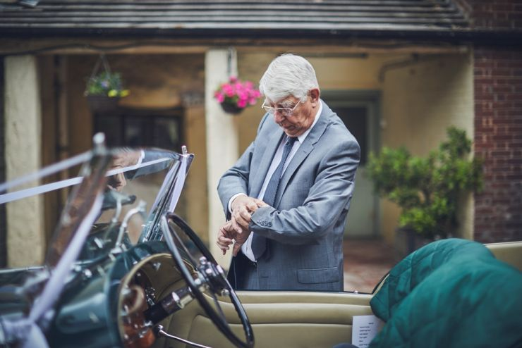 brides grandad checking his watch behind his vintage wedding car
