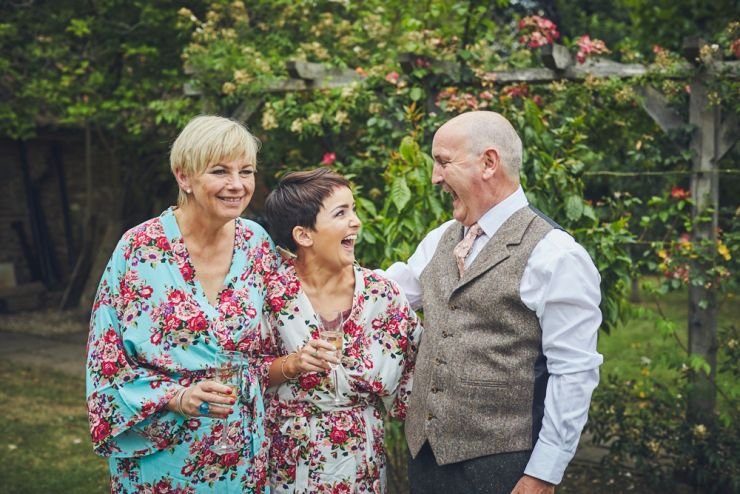 bride to be laughing with mum and dad at home before the Devon wedding ceremony