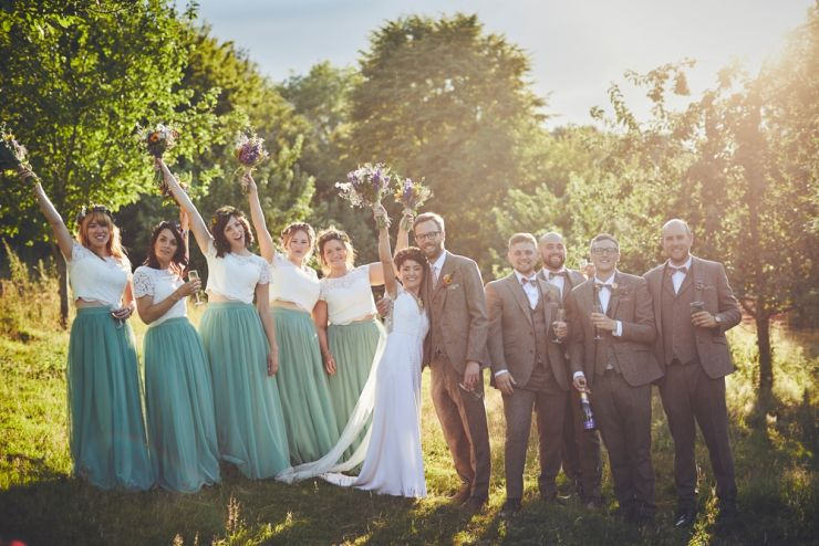 bride, bridesmaids, groom and groomsmen cheering and happy at golden hour in Devon