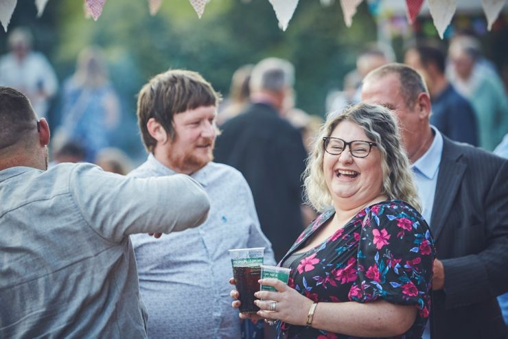 fun wedding photography of guests laughing at a Devon wedding at West Town farm
